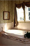 Upscale restroom with garden tub and sunlight in new home Stock Photo