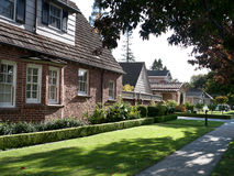 Upscale street with front yards and shaded curb. Brick building with attic Royalty Free Stock Photography