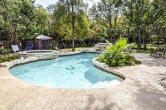 Upscale Swimming Pool in Backyard. A kidney shaped swimming pool with hottub that is surrounded by trees, plants and flowers Stock Photography