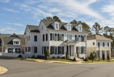 Upscale white family home on street corner. An upscale, white, multi-level family home on a sunny day. House features windows, shutters, and steps and railing royalty free stock photos