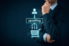 Upselling. On-line (e-shop) marketing concept. Sales technique for more profitable sale. Businessman or marketing specialist think about  - from customers one royalty free stock images