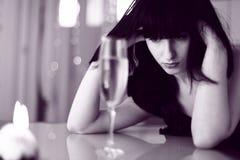 Upset женщина, стекло питья и света candel Стоковая Фотография