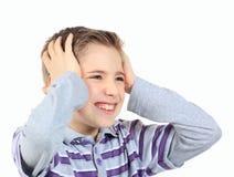 Upset мальчик, держа его руки за его головкой изолированной на белизне Стоковые Фото