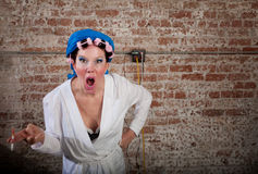 Upset. Lady with pink curlers and white robe stock photo