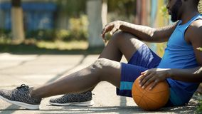 Upset African American basketball player sitting on ground, holding ball. Stock photo royalty free stock photo