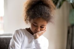 Upset African American girl feel down sitting alone royalty free stock photos