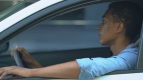 Upset African-American teen boy in hurry waiting in traffic jam, leaning on helm