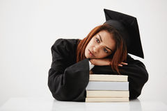 Upset african graduate lying on books thinking sitting over white background. Copy space. Upset beautiful african graduate lying on books thinking sitting over Stock Photo