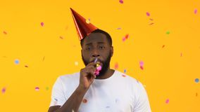 Upset Afro-American man in party hat whistling in horn under falling confetti
