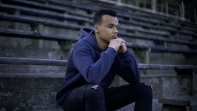 Upset afro-american teenager sitting on tribune, devastation and poverty around royalty free stock photo