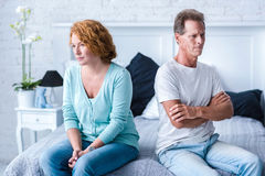 Upset aged couple after a quarrel. I do not understand you. Angry husband and wife sitting back to back on the bed with crossed arms Stock Images