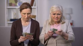 Upset aged female friends holding dollars banknotes, suffering from poverty stock video