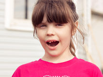 Upset  6 aged girl showing her missing tooth Stock Photo