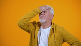 Upset aged man demonstrating face-palm gesture, failure sign, elderly loser stock footage