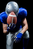 Upset American football player kneeling while holding ball Stock Photography