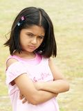 Upset and angry girl. A portrait of a young girl with arms folded and an expression of anger, dissatisfaction and unhappiness Royalty Free Stock Photo