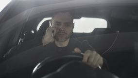 Upset and angry man talking phone while sitting inside car outdoors. Upset and angry man talking phone while sitting inside his car outdoors stock footage