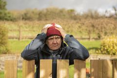 Upset and angry mature woman outdoors. Resting on fence stock image