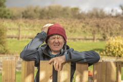 Upset and angry mature woman outdoors. Resting on fence royalty free stock photo