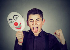 Upset angry screaming man holding clown mask expressing cheerfulness. Portrait upset angry screaming man holding clown mask expressing cheerfulness happiness royalty free stock image