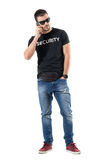 Upset angry undercover plainclothes policeman on the phone looking away. Full body length portrait isolated on white studio background Royalty Free Stock Photos