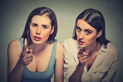 Upset angry women pointing finger an you camera. Upset angry two women pointing finger an you camera isolated on gray wall background Royalty Free Stock Photo
