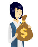 Upset asian business woman with bag full of taxes. Stock Photo