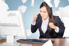Upset asian business woman when working with flying paper scattered stock photo