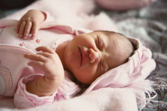 Upset baby. Newborn baby girl wearing pink with frustrated face Stock Photography