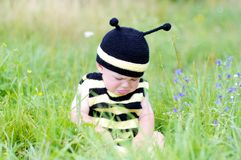 Upset baby in bee costume on the meadow Royalty Free Stock Images