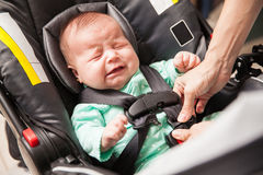 Upset baby being secured in a carrier Royalty Free Stock Images