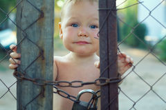 Upset baby looking out of locked wire fencing. Upset baby boy looking out of locked wire fencing. outdoors Stock Photo