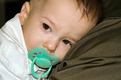 Upset baby with nipple in mouth is leaning on father`s shoulder stock photo