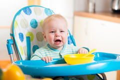 Upset baby sitting in highchair for feeding Stock Photography