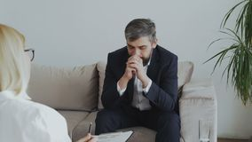 Upset bearded businessman talking about his problems to psychologist in office. Indoors stock footage