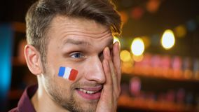 Upset bearded football fan with french flag on cheek making facepalm team losing. Stock footage stock video