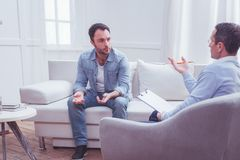 Upset bearded man lifting his hands in dismay during therapy. Personal issues. Full length of upset puzzled bearded men sitting on sofa and lifting his hands in stock photography