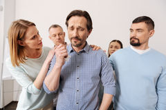 Upset bearded man wrinkling forehead. Do not leave me alone. Command of colleagues standing around their partner putting hands on his shoulder while cheering him Stock Photography