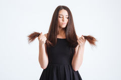 Upset beautiful woman looking on splitting ends of long hair Royalty Free Stock Photos