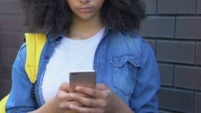 Upset biracial teen girl reading taunting message on mobile phone, cyberbullying. Stock footage stock video footage