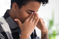 Upset black businesswoman feels unwell sitting in office stock image