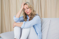 Upset blonde sitting on couch thinking Stock Photos