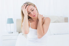 Upset blonde suffering from headache and neck pain royalty free stock image