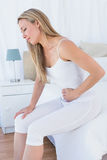 Upset blonde suffering with stomach pain Stock Images