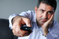 Upset and bored man holding tv remote control zapping TV Channel Stock Photo