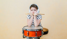 Upset boring little girl sitting, thinking behind a snare drum Stock Photos