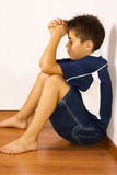 Upset boy against a wall. A young boy sits sad and lonely royalty free stock image