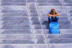 Upset boy covered his face with hands sitting on the stairs outdoors stock photography