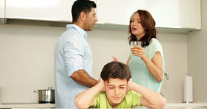 Upset boy covering his ears while his parents fight. At home in the kitchen stock footage
