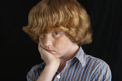 Upset Boy With Hand On Chin Royalty Free Stock Images